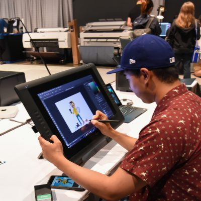 2017 Studio, attendee draws SIGGRAPH mascot Shay D. Pixel at t-shirt printing station